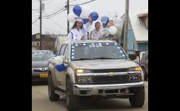 PARADE— NPS Extensions Correspondence School graduate Celina Nadie Habros waves to well-wishers as the graduation parade winds through Nome.