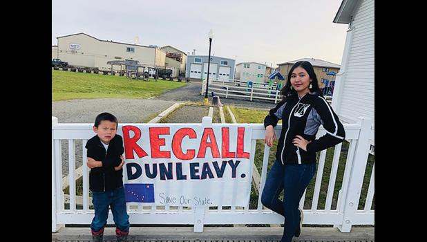 RECALL DUNLEAVY—Benjamin Farley and Evelyn Rochon, who made the sign, stand outside of Old St. Joe's, where a Recall Dunleavy event was held last week as part of a statewide signature gathering initiative to recall Alaska's governor.