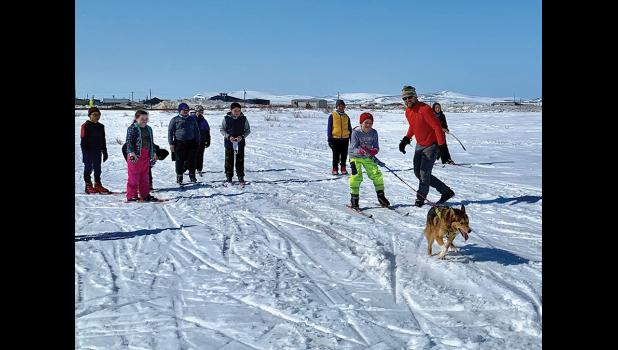 OFF AND RUNNING—Nome Nordic elementary ski coach Leonard Lastine helps fourth-grade skier Jamison Erickson-Ford start her skijor run with Chena. The fourth and fifth grade skiers enjoyed nice end of the season weather as they wrapped up the season.