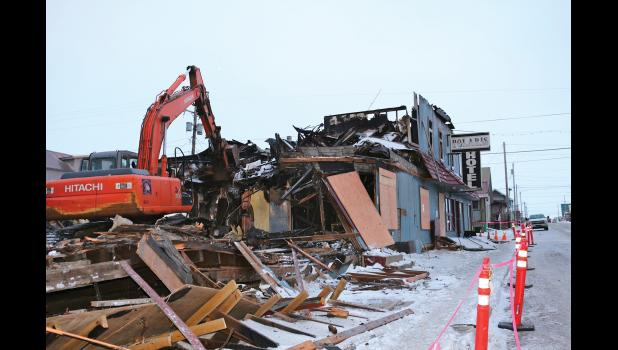 NOW YOU SEE IT—Now you don't. Charles Reader began to take bites of the burned out Polaris Hotel on Nov. 30. The City solicited accelerated bids on Nov. 28 for emergency abatement to begin ASAP with a deadline of Dec. 11. Reader worked through blizzards and high wind over the weekend. By Tuesday, the remains of the package store, hotel and bar complex had gone to the City's monofill.