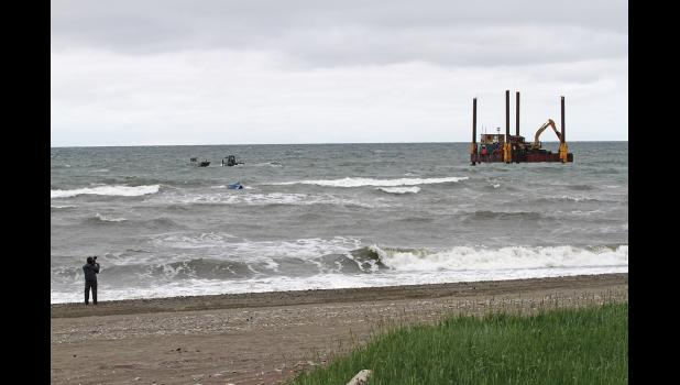 TO THE RESCUE— A cameraman documents the incident as the War Pony skiff bobs in the sea, two skiffs stand by and the jackup rig begins to hoist the platform out of the stormy sea, on Tuesday afternoon.