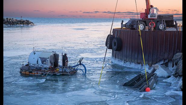 COMING UP— Jeffrey Orzechowski's gold dredge begins to surface with the help of a crane on Monday afternoon in Nome's outer harbor.