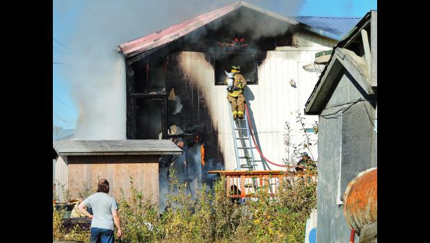 IN FLAMES— A Nome volunteer firefighter points the fire hose into the flames that consumed a five-plex on Fourth Avenue on Sunday evening.