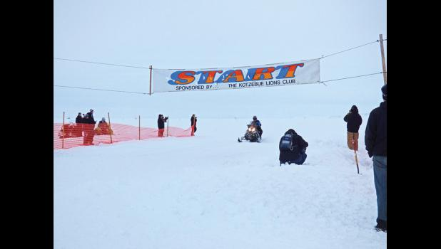 FIRST ACROSS THE FINISH— Mike Morgan of Nome crosses the finish line of the Archie Ferguson Willie Goodwin Memorial snowmachine race in Kotzebue last Sunday, winning the overall title and his class.