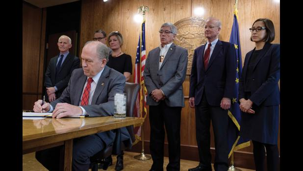 SIGNING—Governor Bill Walker signs an Administrative Order on Climate Change, at the State Capitol in Juneau, October 31, 2017.