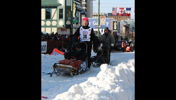 OFF THEY GO— Nome's Aaron Burmeister and kennel partner Tony Browning take off at the ceremonial Iditarod start in Anchorage, Saturday, March 1.