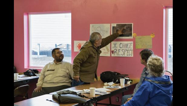 POINTING TO THE FUTURE— Virgil Soonagrook of Gambell refers to a map of his village as he discusses possible economic development at the fourth Arctic Resource Development and Infrastructure summit on Tuesday. Listening to Soonagrook are, left to right, Richard  Koozaata, Louie Green Jr. and Bill Culbertson.