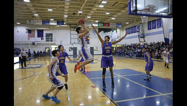 HANG TIME— Nome's Mikey Scott takes to the sky against Barrow's Kamaka Hepa in a game on Friday night. The Whalers went on to beat the Nanooks 92-51.