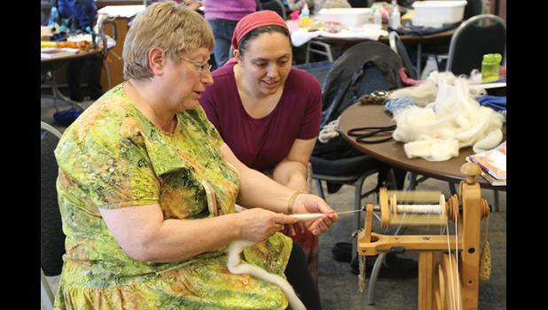 SEE, IT'S EASY(top)— Anita Helsius makes spinning yarn look easy, as Paula Norris looks on during last week's Fiber Fest held at the XYZ Center in Nome.