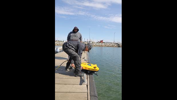 DEFENDER— Wales' Clyde Oxereok launches the Defender ROV into the Nome small boat harbor as Walter Ozenna of Diomede looks on, during a training session on Wednesday, June 12. SAR volunteers were trained for several days last week to use the newly purchased equipment by NSEDC to assist in search and rescue operations regionwide.