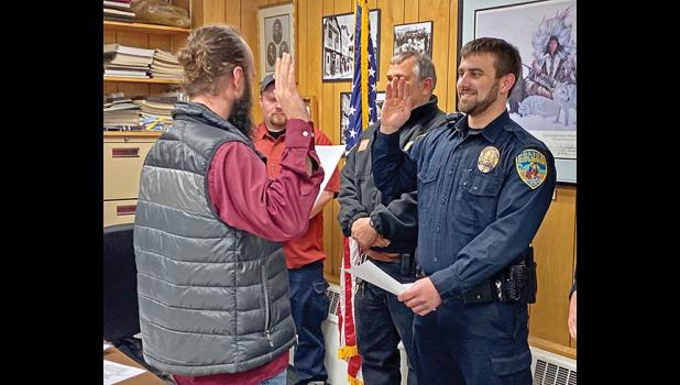 HE SOLEMNLY PROMISES—Austin Martino, newly hired Nome police officer takes his oath of office administered by Bryant Hammond, city clerk. Martino comes from New York.