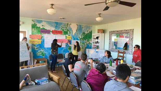 """LEARNING TOGETHER— A two-week language workshop titled Ilisaqativut brought 20 learners of Inuqpiaq to Nome for two weeks. Qunmiġu Kacey Hopson and Annauk Denise Pollock, center, hold a phrase that translates into """"How do you write that in Inupiaq?"""""""