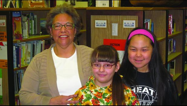 """ART—Alaska Native Culture teacher Josie Bourdon worked with students Iryna Kadustka and Kaitlyn Moses on their art projects, """"Many Lands, One Arctic."""" The videos the girls made are on display at the Art Center in Juneau."""