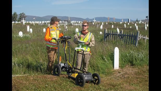 EARCHING FOR UNMARKED GRAVES— Logic Geophysics used ground penetrating radar to search for unmarked graves. Dr. Esther Babcock, left, analyzes the data. Caleb Babcock supplies the muscle.
