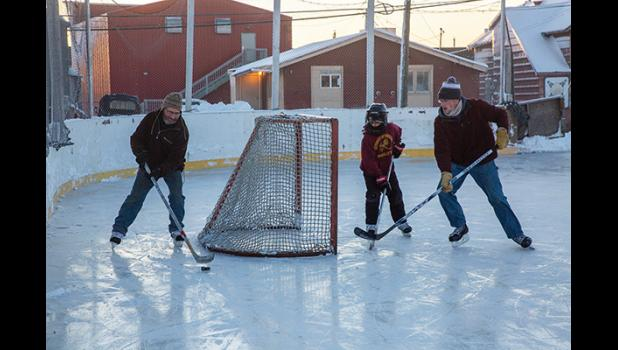 HOCKEY TIME— James Erickson, left, and his sons keep the puck moving on Nome's ice rink Saturday. The ice is nice and the rink is open for skaters.