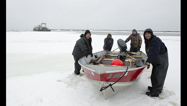 RETURN — Back at the port following a hunt in difficult weather, the crew pushes the boat up the ice to the trailer. They are Ben Apassingok, Lonnie Booshu, Joe Cross III and David Booshu.
