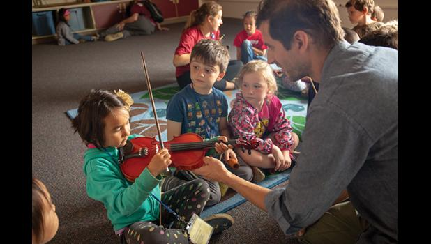 HELPING HAND—Warbelow Range's Kyle Sanna gives Jadelynn Messer tips for playing the violin while Glazier Culley, center, and Gwinevere Dillman observe. Warbelow Range was this year's guest band during the Nome Summer Music Festival, held last week.