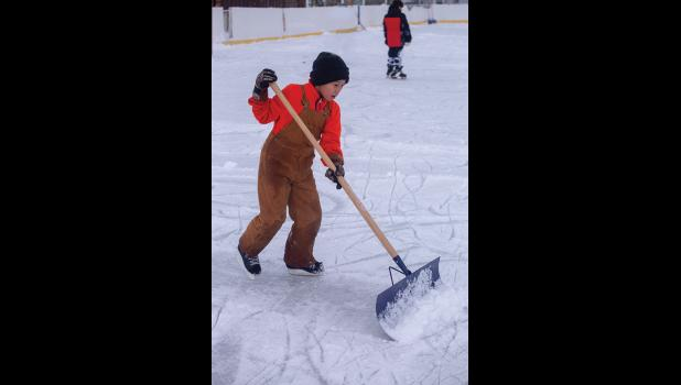 SNOW REMOVAL—Kurt Nattanguk, age 9, does his part to keep the Nome ice rink in top condition while skating Friday afternoon.