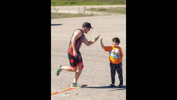 Matt Culley high-fives his son as he crossed the finishline of last week's Strok'n Croak